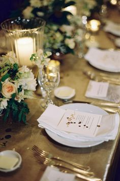 beautiful tablescape with shiny gold tablecloth, alternativing flower and candelit hurricane centerpieces and menu with confetti