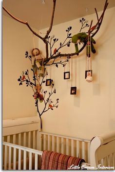 Tree decals combined with real branches create a place to hang pictures and toys.