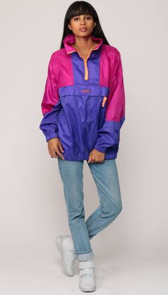 """Vintage 90s windbreaker jacket by Columbia in purple and magenta colour block with a neon orange zipper. Pullover style with a half zip and a big pocket.  Every item we sell is authentic vintage and one-of-a-kind! You will receive the EXACT item shown in the photos. For reference, model is 5'7"""" and measures 32-23-34. DETAILS  Best fits: labeled Extra Large (Note: We only have ONE in stock. If more than one size is listed it is because this item will work on a range of sizes. Check…"""