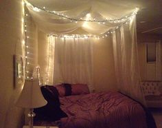 DIY canopy bed using command strips, sheer curtains, and wire ornament hooks