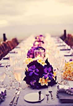 Beach wedding reception table decor. Looks like something straight out of a movie! Low flower arrangements make it easier for your guests to chat too