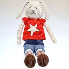 This Crocheted Boy Bunny has a bright red top on with a white star in the middle. Handmade by the ladies of Hathay Bunano in Dhaka, Bangladesh. Part of the 'Pebble' range of baby toys.  Machine washable - 100% Cotton outer - Polyester fill - Suitable from birth  Width : 120mm Height : 370mm Thickness : 70mm Ear Length : 100mm