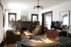 Rachel Denbow's lovely living room via A Beautiful Mess. dark, thick trim. black brick fireplace. graphic rug. aqua piano
