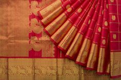 A stunning Kanjivaram with shades of red set in broad stripes across the sari.