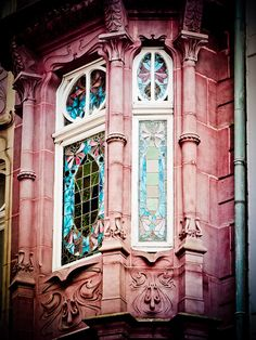 Beautiful stained glass in turquoise tones inset in rose-colored carved stone or marble, in Luxembourg