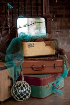 Vintage luggage sits beneath the wishing tree embellished with rhinestones, hanging chandelier lighting and vintage hawaiian postcards.