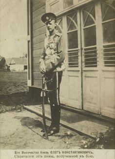 Postcard do Príncipe Oleg Constantinovich, em 1914. Ele está em pé voltado em parte para à esquerda com uma porta atrás dele. Ele está vestindo uniforme militar e está segurando uma espada com ambas as mãos. Há uma legenda em russo abaixo.
