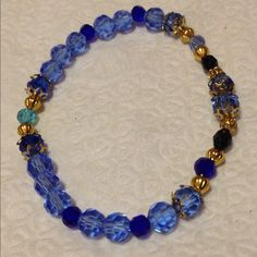 Stretch Band Bracelet Handmade Stretch band Bracelet. Colors are royal blue, sky blue, aqua and black with gold fixtures. Jewelry Bracelets