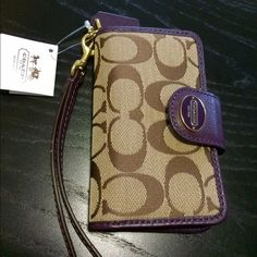Coach signature phone wristlet Traditional khaki print with violet leather and gold metal detailing. Never been used, and it still has tags attached. I believe it's for an iPhone 4 or 5, it does NOT fit an iPhone 6. It has a snap closure, leather wrist strap and a camera opening in the backside of the wristlet. Coach Bags Clutches & Wristlets