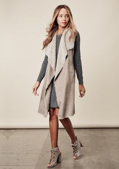 """Super soft, faux suede, blanket vest in a maxi silhouette. Vest features pockets, drapey shawl collar and luxurious faux fur interior. Sophisticated and chic. 100% Polyester Model is 5'8"""", wearing siz"""