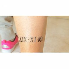 Little calf tattoo of a date in roman numerals on Patri.