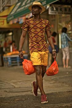 Lougè Delcy wearing an African print straw hat by Brixton, Zara Tee, yellow HM x Marni shorts, Cole Haan Wingtip Espadrilles, Atrium Nixon Watch. Shot by Koo Location | Chinatown, New York