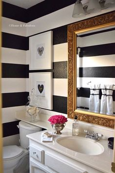 Baño con muro bicolor de líneas horizontales blancas y negras, los muebles del baño son blancos y sobre el vanitorio un espejo rectangular de marco dorado estilo rococó.