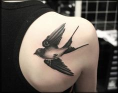 black ink bird on the shoulder is a cute tattoo that signifies someone's free spirit
