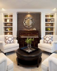 Living room with taupe accent wall, white built ins, white club chairs and brown leather ottoman.