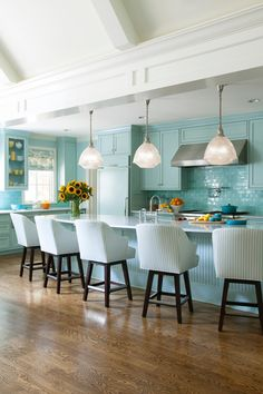 Mornings must be fun in this cheery blue transitional kitchen. A long island offers up lots of room for casual dining and hanging out while a vaulted ceiling adds to the open airy feel.