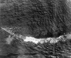 8 in heavy cruiser Chikuma, second of the 2 ship Tone class, during the air attacks which sank her at the Battle of Leyte Gulf on 25 October 1944.  Destroyer Nowaki picked up many of her crew, but was herself sunk the next day, leaving only one Chikuma survivor.  This class grouped all their 4 x 8 in turrets forward to increase seaplane carrying capacity aft.