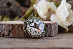 This necklace features a pendant with a beautiful woodland picture: the lovely image of a hummingbird in the foliage. The pendant has been sealed with a magnifying glass dome, to protect and enhance the image.  ∞∞∞ M e a s u r e m e n t s ∞∞∞ Measures approx: • Glass dome: 25mm / 1 in diameter • Pendant base: 32mm / 1.26 in diameter  Please select chain length.  ∞∞∞ S i m i l a r P i e c e s ∞∞∞ To see matching pieces for this item, take a look here…