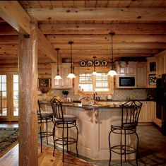 An open kitchen with custom maple cabinets and granite countertops in this log home ensures you won't be cut off from guests when preparing meals.