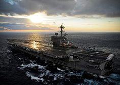 Sunrise over an aircraft carrier.