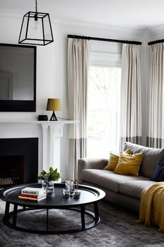 living room in an original 1930's Melbourne house brought to life by Robson Rak Architects - lovely colour palette of soft grey with mustard accents. Coffee table is the Obi by Linteloo