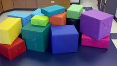 love this idea - wrap boxes with bulletin board paper to make cubes for displaying artwork.