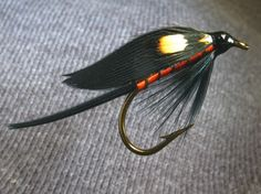 Lord-Baltimore- Tail, black quill fibres, Body, orange floss, Rib, black silk floss, Beard, black hackle fibres, Wing black with jungle cock eye.
