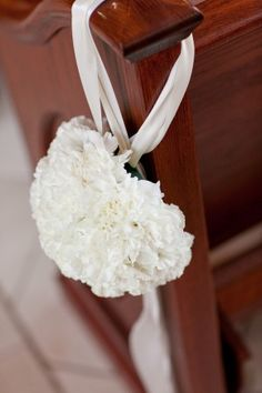 cute. could use carnations, silk or real, and cut foam balls in half so they lay clean against the pew