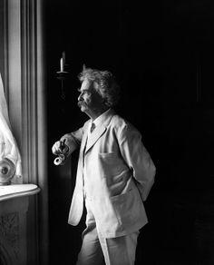 Mark Twain (Samuel L. Clemens, 1835-1910) American humorist standing by window in 1907 portrait.