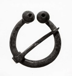 Copper alloy penannular brooch: cast; oval section hoop with poppy-head terminals, a hole in top of each; pin with head of coiled strip.