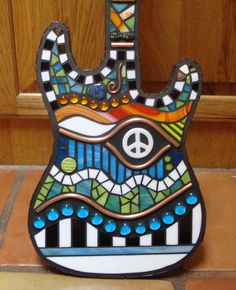 This is my peace guitar that I made out of stained glass, copper, beads, mirror, ceramic tile, glass rods, and vertreous glass