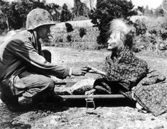 (1 April 1945). As the Marines landed on Okinawa, the Japanese military fled, leaving the aged, the infirm, and the too-small children in the path of the Leathernecks. Marine Corporal Fenwick H. Dunn of Lynn, Massachusetts, shares the candy from his K ration with an aged woman.