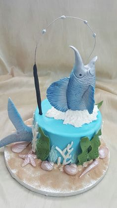 Buttercream finished cake with fondant fish and other decor for a very special husband and son's birthday.