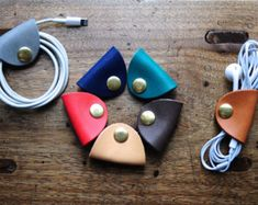 MUST HAVE: Leather handmade earphone holders can also be used for many other things like bracelet holders, wire organizers, pony tail holders, and more. $7 on Etsy!!