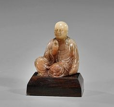 """Small Chinese Carved Soapstone Lohan Small Chinese carved soapstone Lohan; the sitting deity in """"Royal Ease"""" with decorative robes and inlaid gems, of pale red suffusions; H: 2 1/2""""; wood stand"""