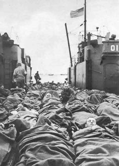 Wounded American soldiers on board a landing craft in Normandy ready for transfer to a hospital ship, which will take them to England, August 1944.