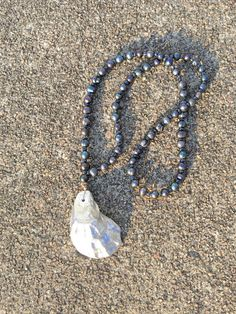 36 silver oyster shell necklace. The beads are a dark, iridescent pearl. Each bead is shaped a little differently. The wire on the shell is gold as