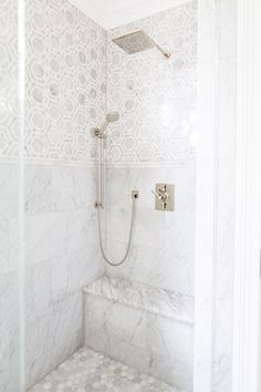 The large scale of the mosaic tile creates the illusion of a space, while a tall wainscot in the shower gives the room balance and proportion. Clayman used a curbless shower for its clean lines and modern aesthetic   archdigest.com