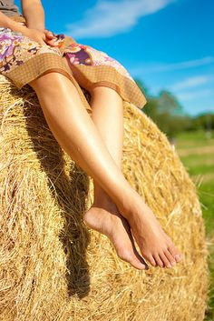 Sitting on a hay bale in the sun.
