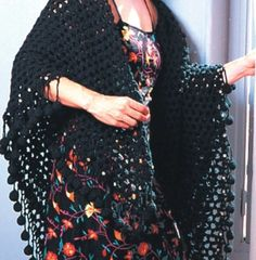 """Crochet a lovely black shawl in an openwork pattern with fun crochet ball trim. Instructions to make the crochet """"bobbles"""" included. This crochet shawl from DMC Threads is a great way to wrap up in the evenings.  Free pattern."""