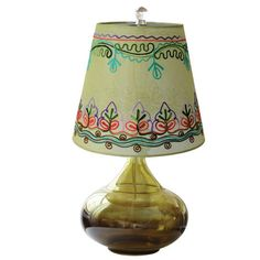 Green glass lamp with an embroidered floral shade.    Product: Table lampConstruction Material: Glass and cotton