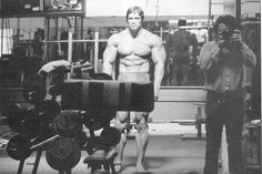 ILYKS.COM - Arnold Schwarzenegger looking into mirror with camera man visible in mirror taking a shot of his stature Hulk