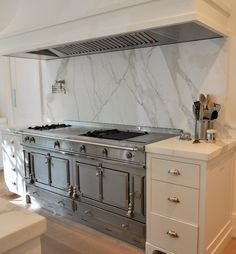 Gorgeous La Cornue Serie Centenaire 100th Anniversary Range, pot filler, wood panel range hood and marble backsplash.