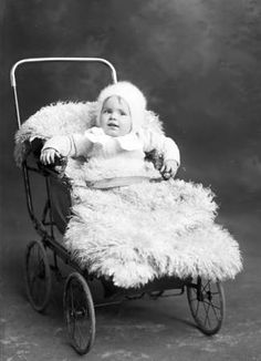Baby girl, identified as Adah May, in a baby carriage, antique Edwardian photo, 1910.