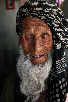 An old Muslim man pauses to have his portrait taken outside of a shop in rural Kashmir.