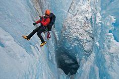 Fotografía de James Balog  Para documentar los cambios en el casquete de hielo, Michael Brown desciende hasta un molino, un pozo vertical o sumidero creado por la fuerza del agua de fusión.