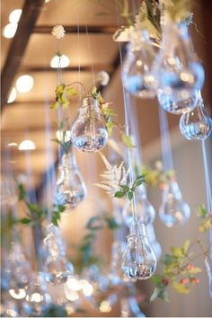 LOVE this idea! Upside-down glass lightbulbs make the most whimsical hanging decorations when filled with a sprig of greenery.
