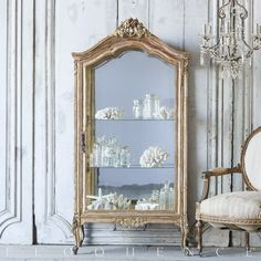 Eloquence, Inc. Vintage Vitrine Fabulous vintage vitrine from the Mediterranean coast. In a distressed gilt finish, with pretty curving Louis XV legs and an ornate carved floral crest. Two glass shelves inside provide display space for your favorite treasures.