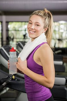 Woman on treadmill holding water bottle at gym stock photo