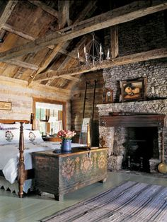 Dark interiors are brought to life with the addition of clean white bedding and linens. Floral details on the shams and duvet serve as a rustic compliment to the raw oak in the exposed support beam and dry-stacked hearth with stones that could otherwise be bulky and cold. Additional feminine details like the painted, antique chest at the edge of the bed, aged chandelier lend themselves to creating a comforting cottage appeal.